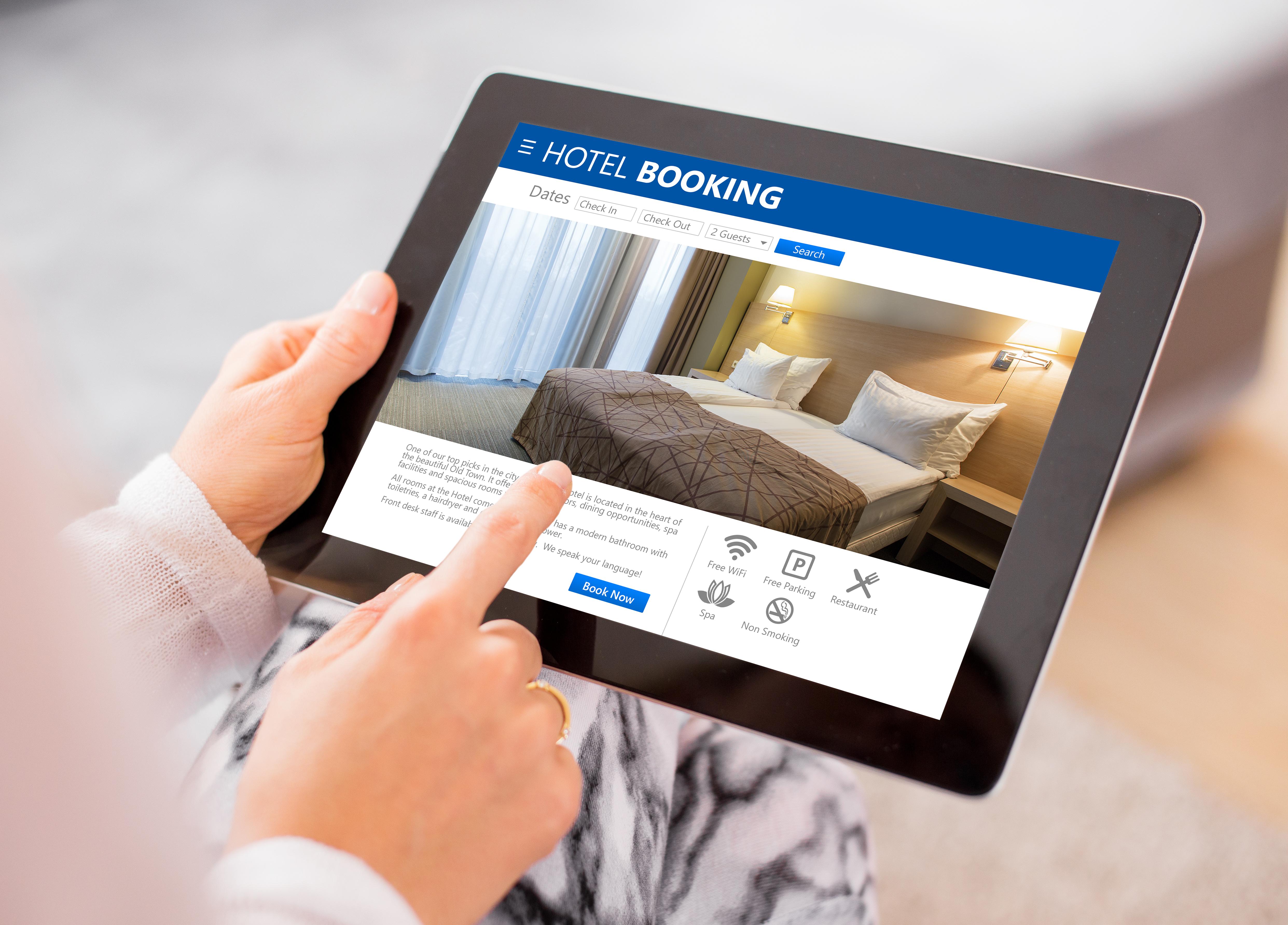 Donna con tablet che sta prenotando online una stanza d'albergo