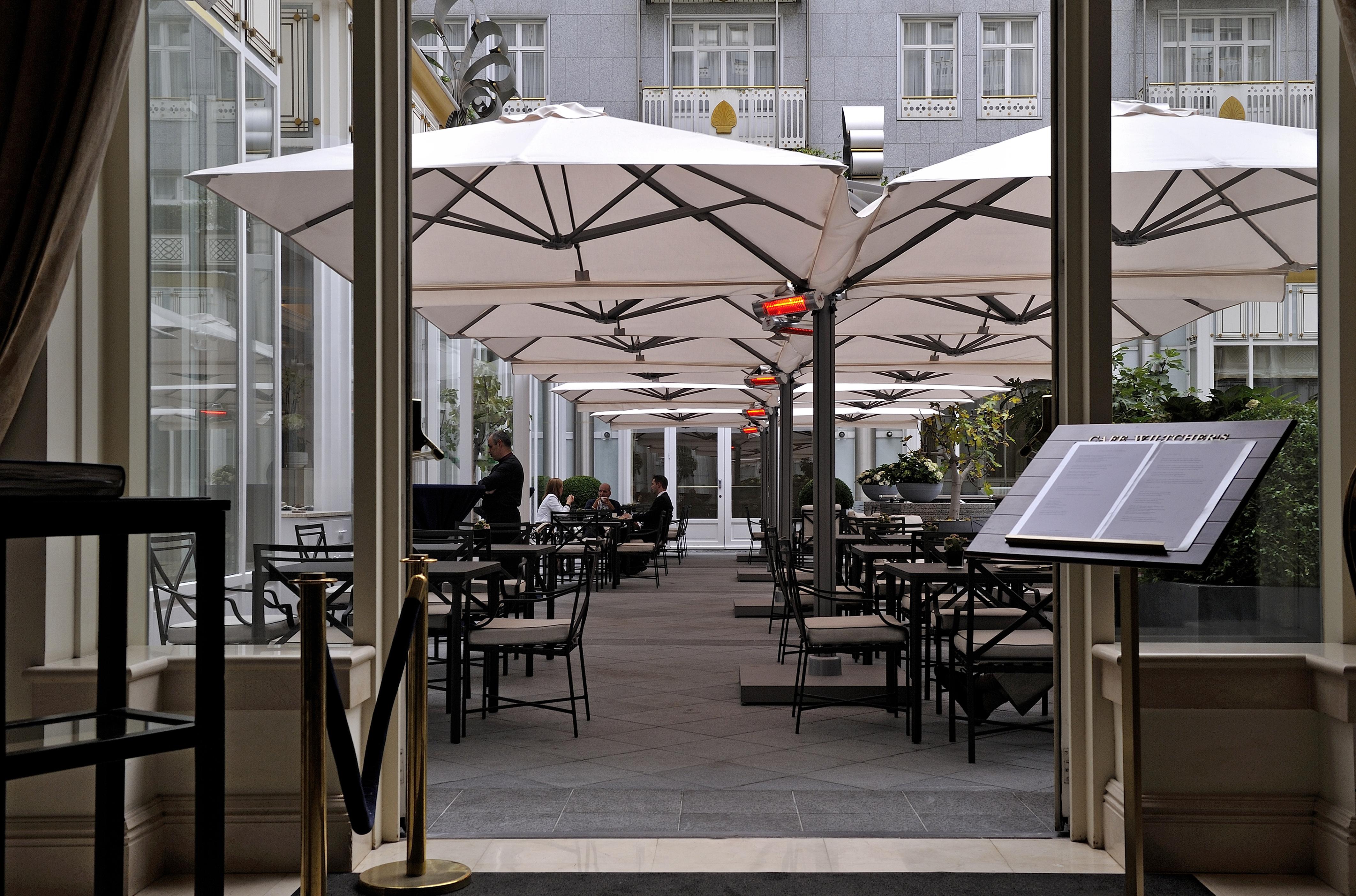 Una serie di ombrelloni componibili MaPro P6 nella corte interna di un hotel