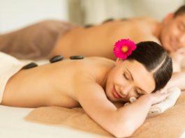 Uomo e donna su lettino durante un trattamento spa di coppia