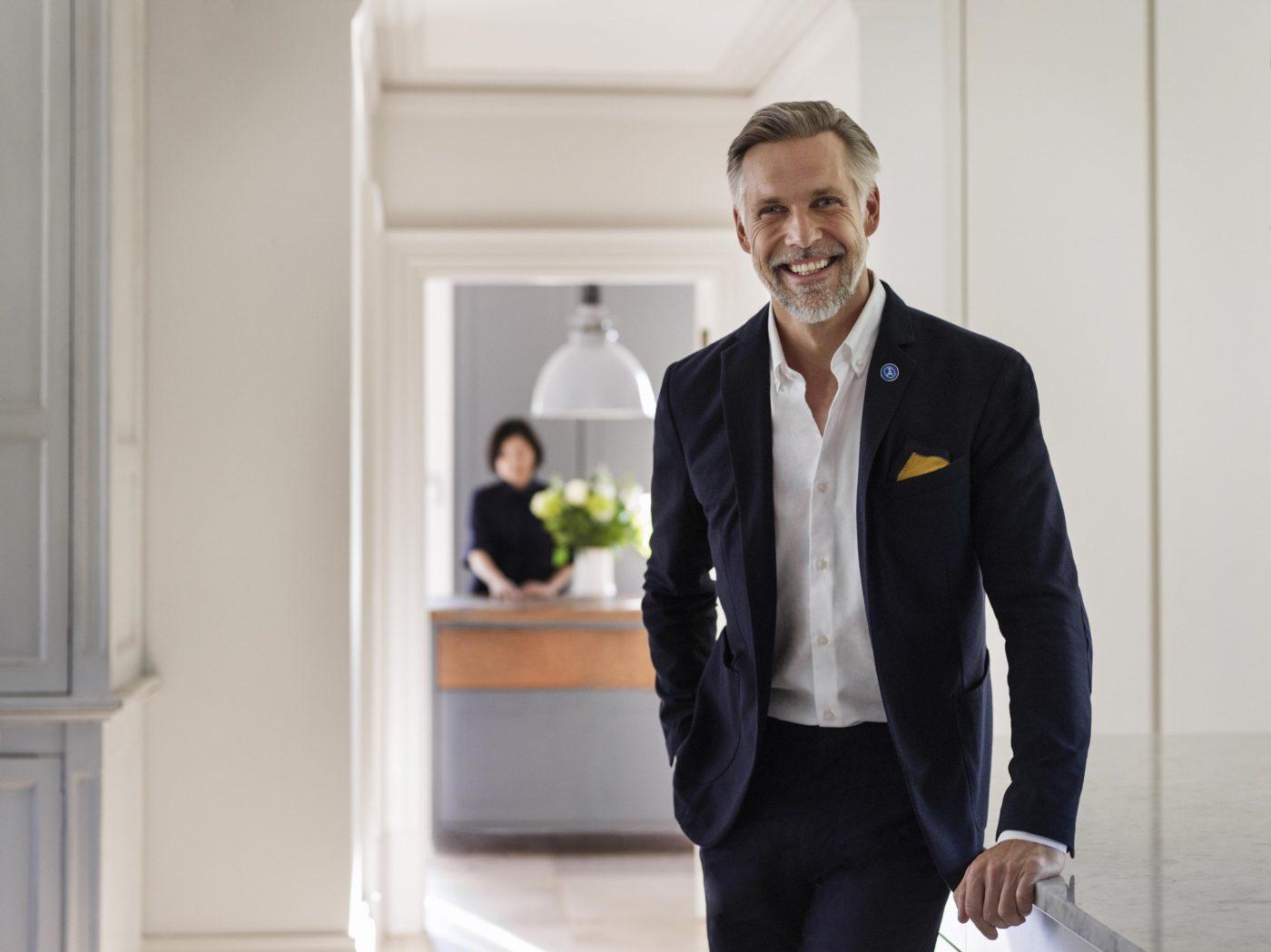 IHG, uomo sorridente pronto ad accogliere l'ospite in un hotel del nuovo brand voco