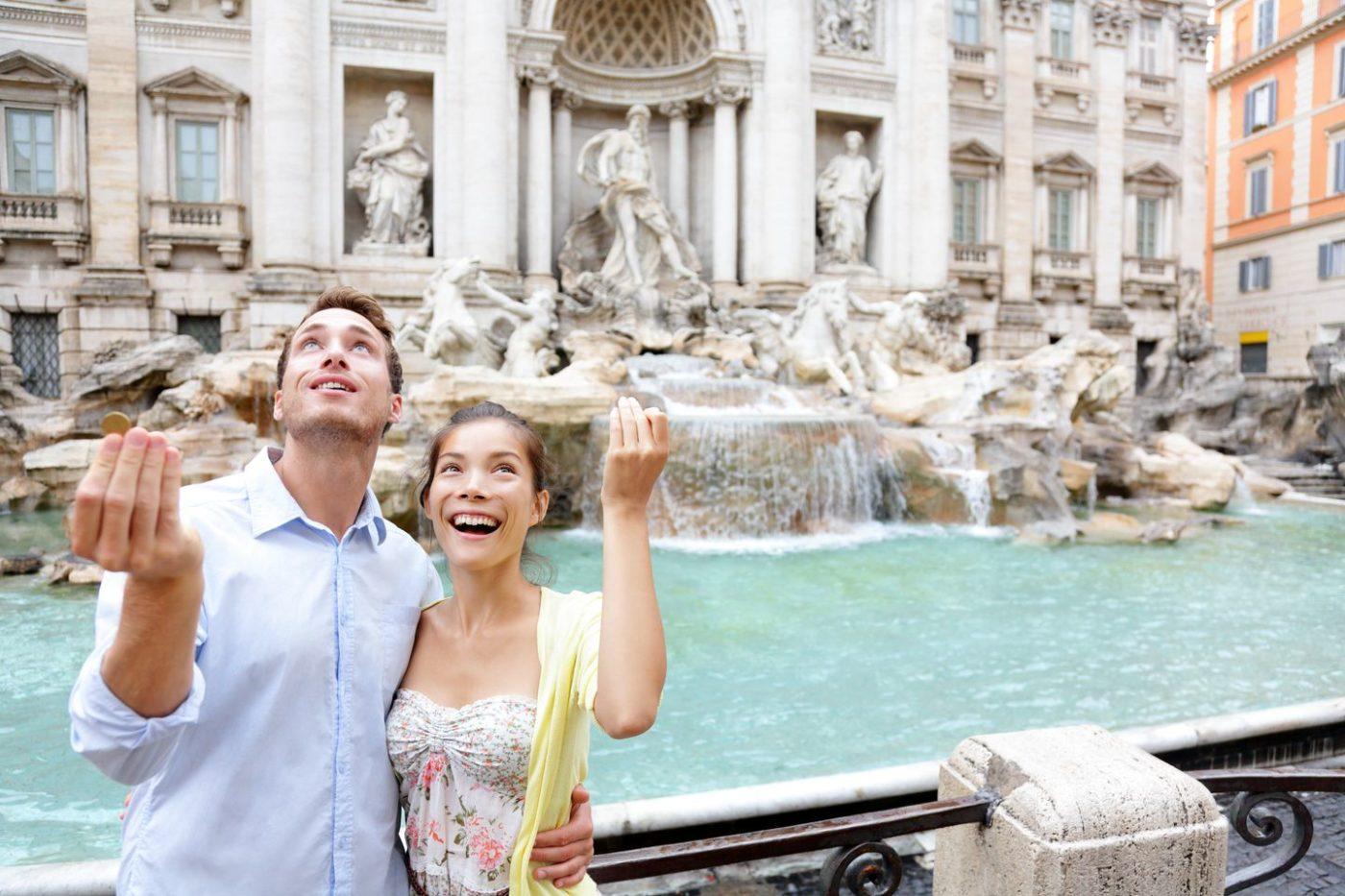 Una coppia di turisti stranieri lanciano la monetina nella fontana di Trevi a Roma