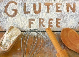 attrezzature da cucina su un piano di legno infarinato e la scritta gluten free