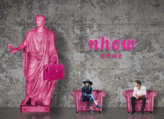 Uno scorcio del nhow Rome, con una statua che richiama la Roma classica di colore rosa e due persone sedute su poltroncine rosa