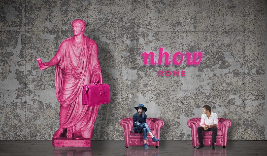 Un rendering del nhow Rome, con una statua di colore rosa e due persone sedute su poltroncine rosa