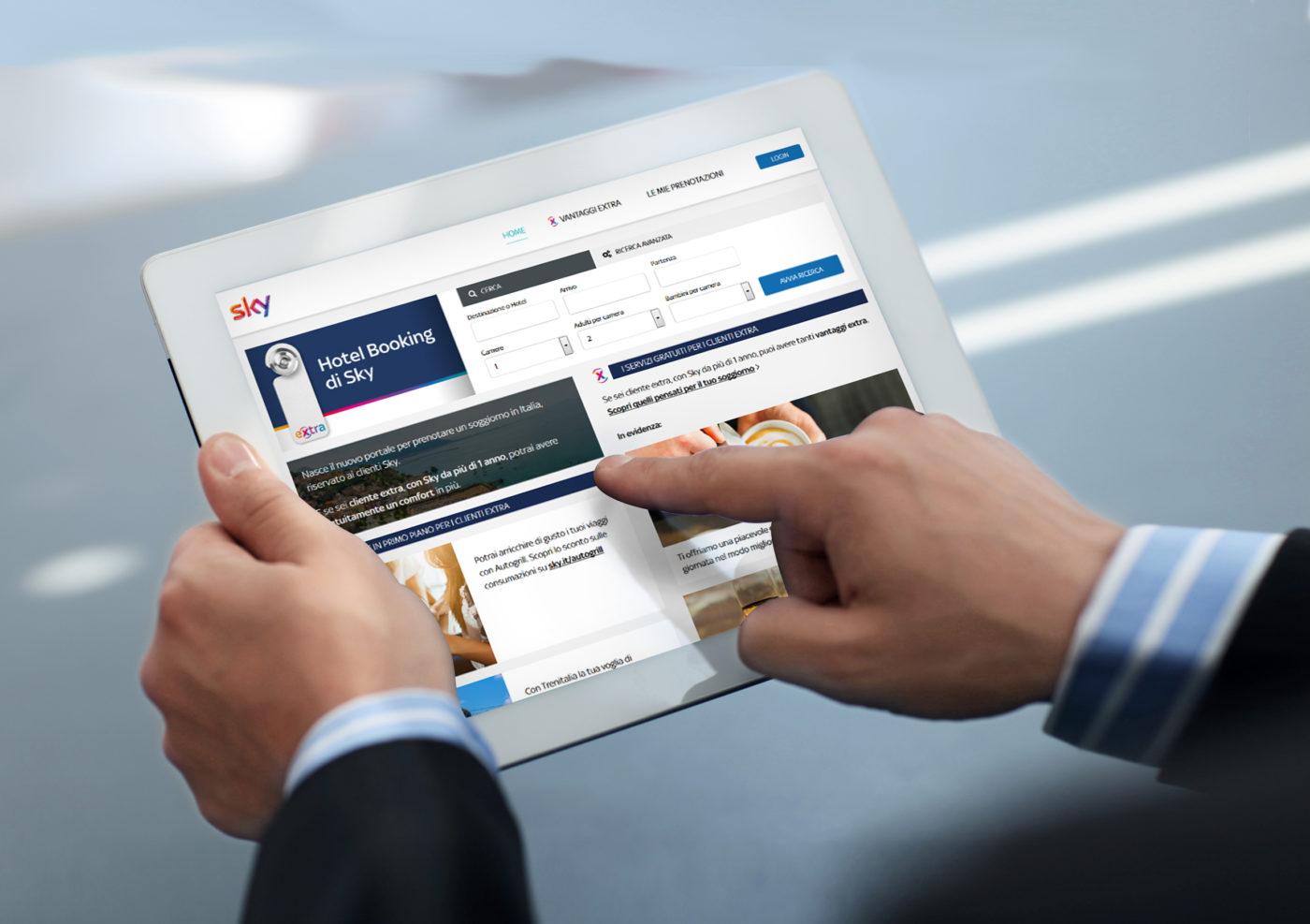 Un uomo d'affari prenota un soggiorno da un tablet con Hotel Booking di Sky