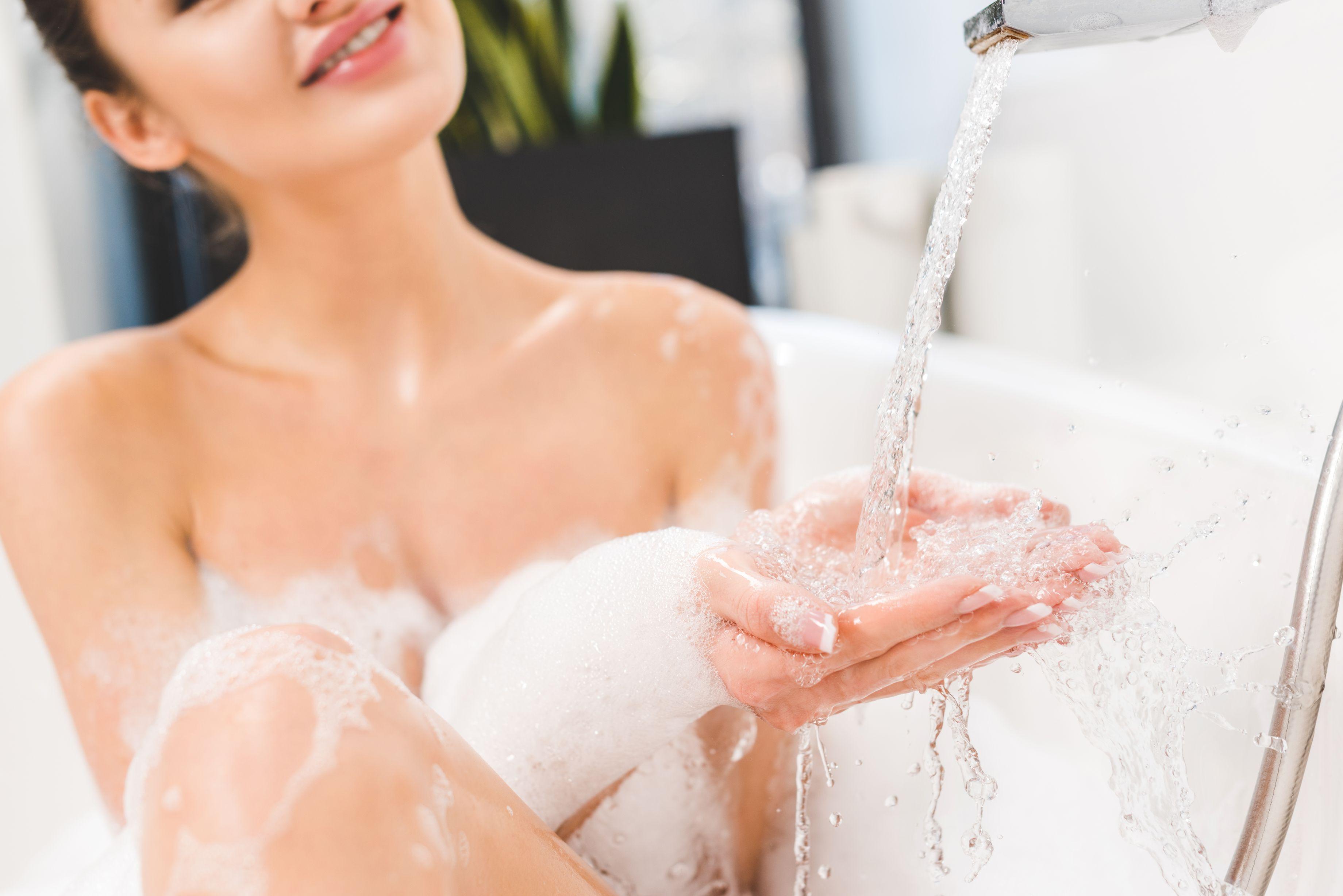 Una donna in vasca con il rubinetto dell'acqua aperto