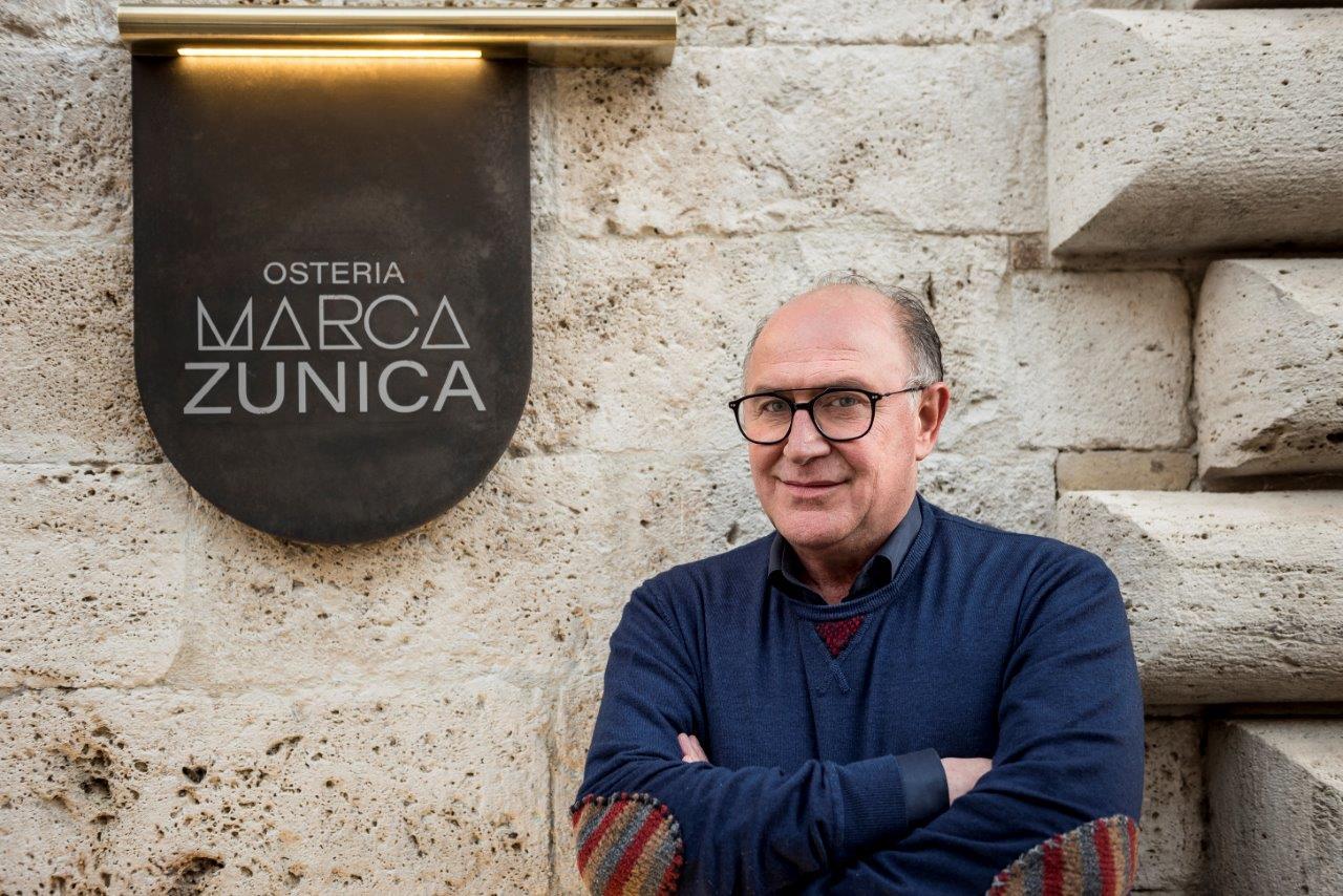 Daniele Zunica di fianco all'insegna del ristorante Osteria Marca Zunica